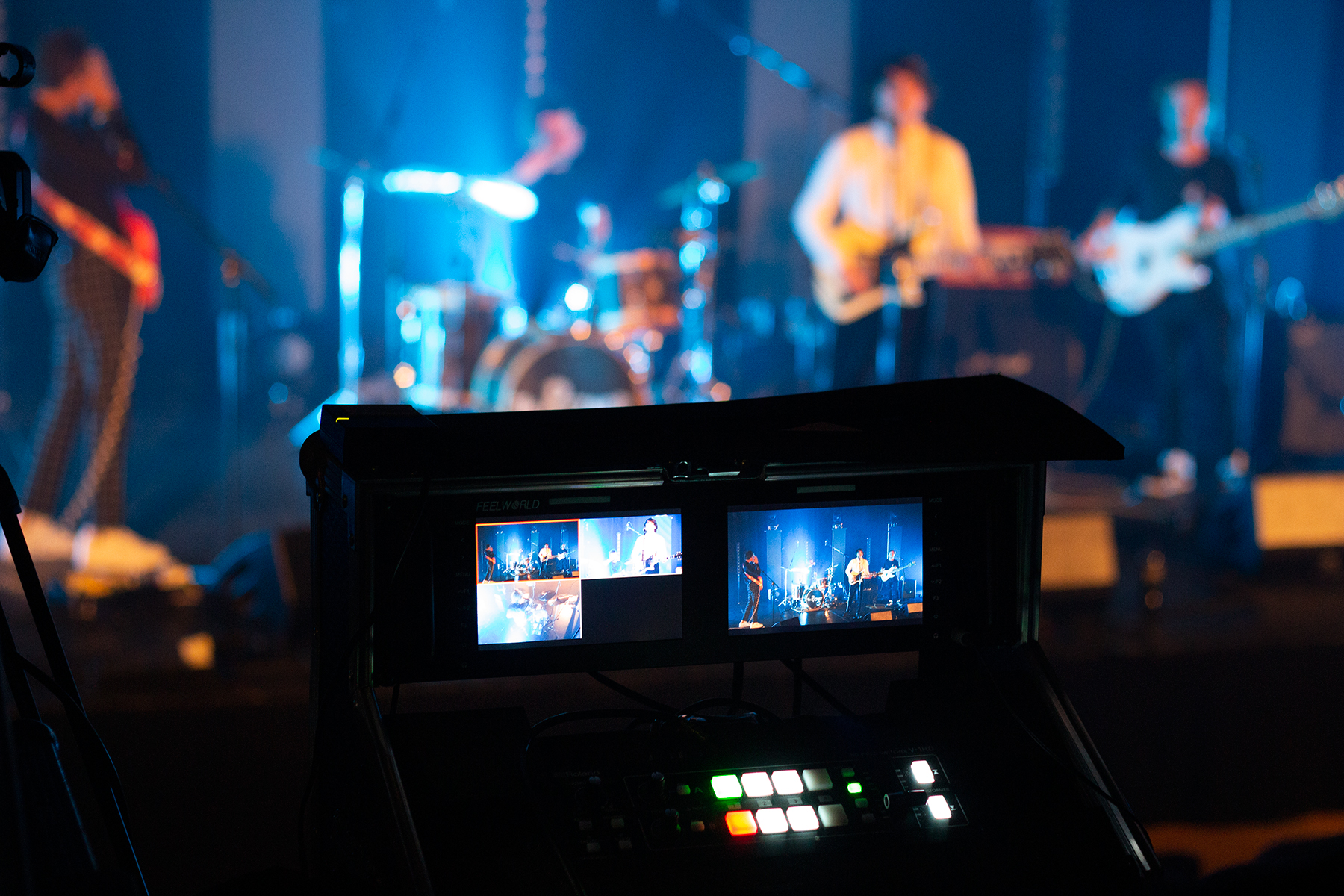 mixed-focus shot of a band performing behind a video monitoring setup